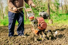Man preparing garden soil with cultivator tiller - stock photo