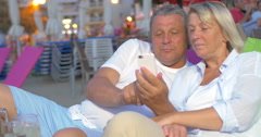 Mature couple using smart phone on the beach Stock Footage