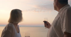 Mature sweethearts enjoying sea view and wine Stock Footage