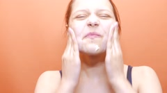 Young woman washing scrubbing face with facewash soap scrub. 4K UHD - stock footage