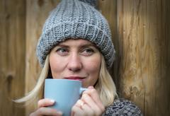 Beautiful blonde female drink coffee uoutdoor - stock photo