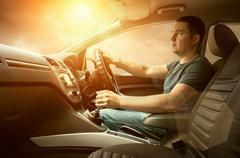 Man sitting and driving in the car under sunset sky - stock photo