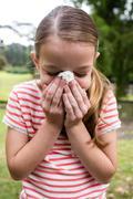 Sick girl sneezing in the park Stock Photos