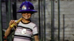 1964: Middle school aged salutes military march fireman hat costume. - stock footage