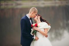 Love and passion - kiss of married young wedding couple near lake Stock Photos