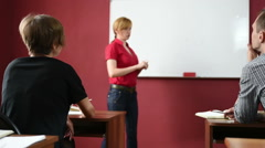 Female teacher giving a lecture at the University. transmits notebook Arkistovideo