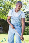 Young man in dungarees raking the garden Stock Photos