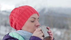 Portrait of young beautiful woman drinking tea or coffee from a thermos cup HD Stock Footage