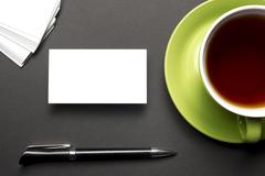 Business card blank over coffee cup and pen at office table. Corporate Kuvituskuvat