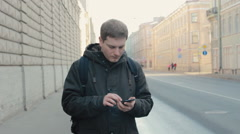 Young man with a cellphone looking for the right way on the street of a big city - stock footage