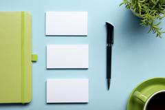 Business card blank, notepad, flower, coffee cup and pen at office desk table Kuvituskuvat