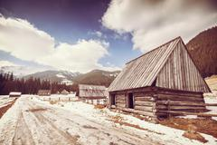 Old film retro stylized wooden hut by a road in Tatra Mountains. Stock Photos