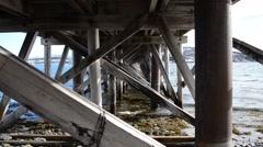 Waves hitting old wooden bridge poles underbelly Stock Footage