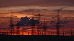 4K Video: electrical utility polw in sundown with clouds and a orange sky Stock Footage