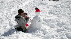 Two brothers playing together with snowman Stock Footage