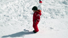 Baby kicking snowball together with snowman Stock Footage