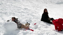 mum and two children playing with snowballs - stock footage