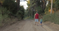 Grandpa and grandson having evening walk in woods Stock Footage