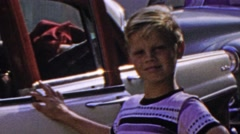 1964: Dad working in car while son admires classic beauty. Stock Footage
