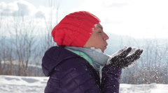 Young woman blowing snowflakes from her hands in a winter day, slow motion HD Stock Footage