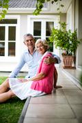Senior couple sitting on steps outside house in yard - stock photo