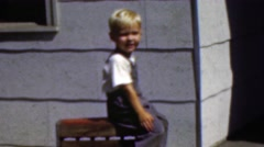 1964: Cute blonde kid blowing kiss seated outdoor sunny summer. Stock Footage