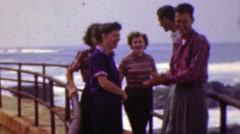 1961: Teenagers hanging out rusted iron pier oceanside. Stock Footage