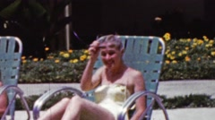 1961: Women suntanning poolside lawn chairs bathing suits lounge. - stock footage