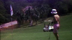 1963: Women removes golf green pin putting for birdie driving cart. Stock Footage