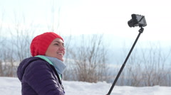 Young woman hiker using a selfie stick in the mountains HD Stock Footage