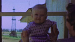 1957: Mother raises baby near oil drilling derrick in backyard. Stock Footage