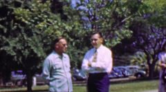 1957: Men talking important serious business on a Sunday in a park. Stock Footage