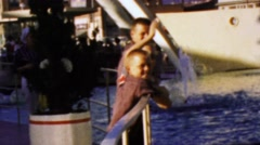 1964: Young boys enjoying cultural beauty of water fountain sculpture. - stock footage