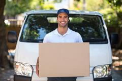 Portrait of smiling delivery person holding cardboard box Stock Photos