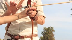 Archer trains tourist boy how to shoot a bow at the historical festival Stock Footage