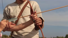 Archer trains tourist boy how to shoot a bow at the historical festival - stock footage