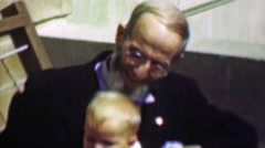 1958: Sharply dressed old grey bearded grandpa holds baby boy. Stock Footage