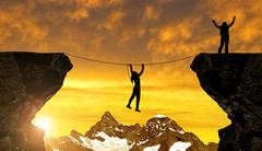 Silhouette girl climbs on a rope over an abyss Stock Photos