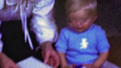 1958: Baby underwhelmed at crab food bib gift that mom unwraps. Stock Footage