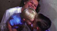 1958: Mom enjoys kid brothers kissing bedtime goodnight. Stock Footage