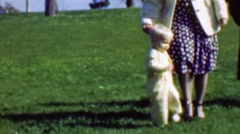 1961: Mother training baby walk falls down trying learn legs. Stock Footage