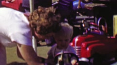 1961: Young blonde boy rides car carnival carousel amusement park. - stock footage