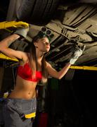 Beautiful young female mechanic inspecting car in auto repair shop. Sexy Stock Photos