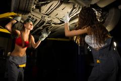 two Beautiful young female mechanic inspecting car in auto repair shop. Sexy - stock photo