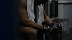 4K MMA fighter sits alone in locker room, psyching himself up before a fight Stock Footage