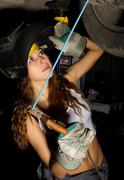 Beautiful young female mechanic inspecting car in auto repair shop. Girl welder Stock Photos