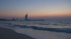 Burj Al Arab beachfront hotel at sunset water sea Dubai landmark attraction day  Stock Footage