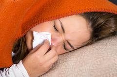 Brunette lying down under orange blanket and blowing her nose, sick with flu - stock photo