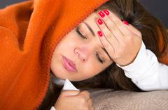 Closeup brunette headshot lying down under orange blanket and blowing her nose - stock photo