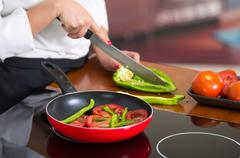 Closeup chef cutting green peppers on wooden surface with red skillet in front Stock Photos